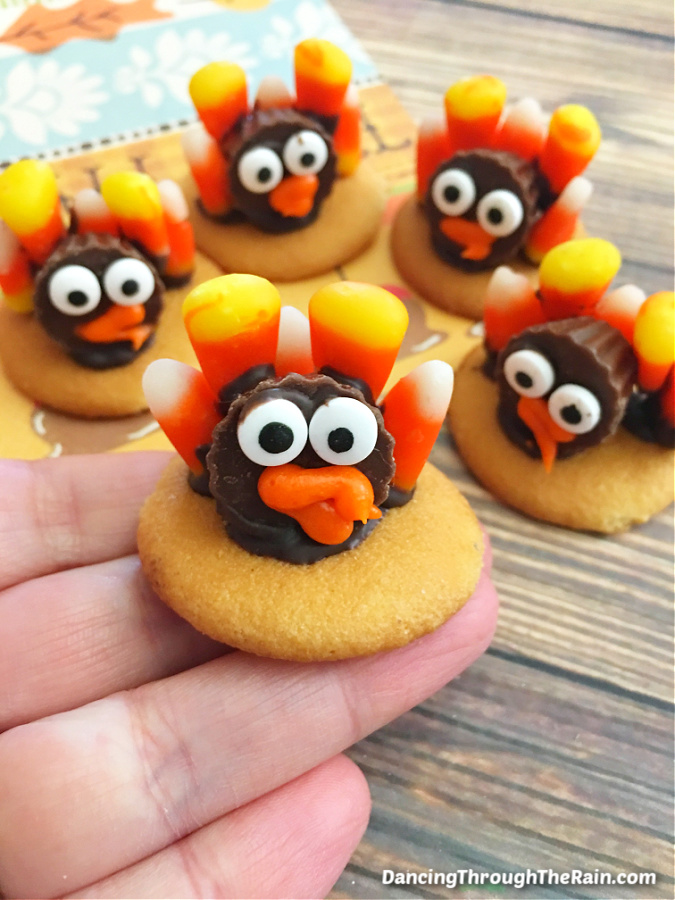 A hand holding Candy Corn Turkey Cookie with four more on the wooden table in the background