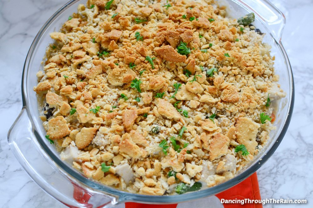 A clear round dish full of Tetrazzini Casserole on an orange placemat