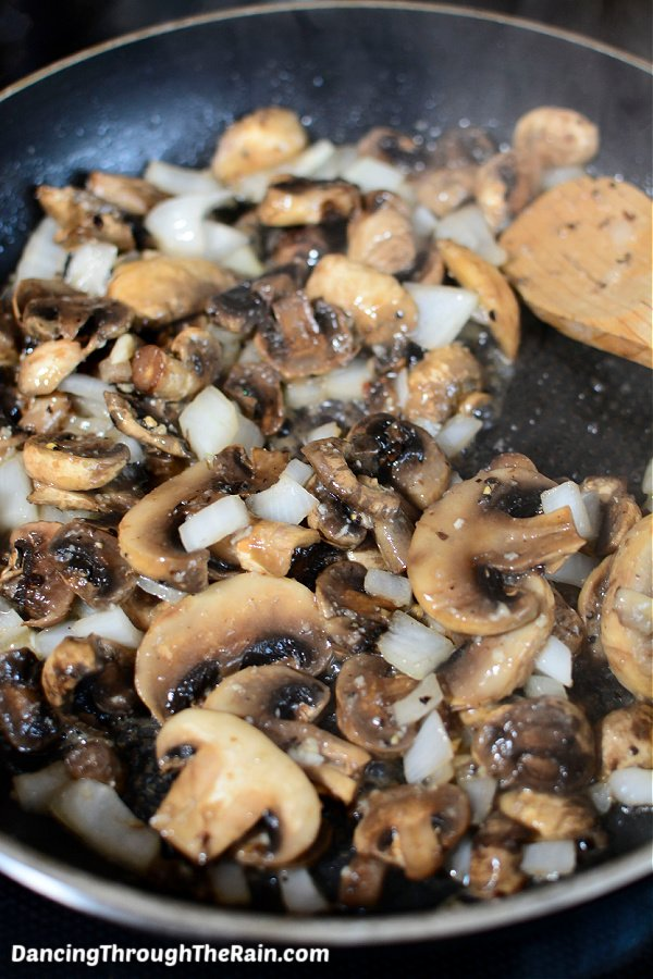 A black skillet with mushrooms and onions cooking with a wooden spoon
