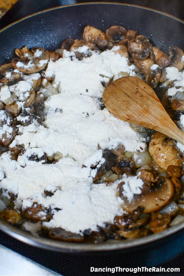 A black saucepan with mushrooms, onions, and flour with a wooden spoon