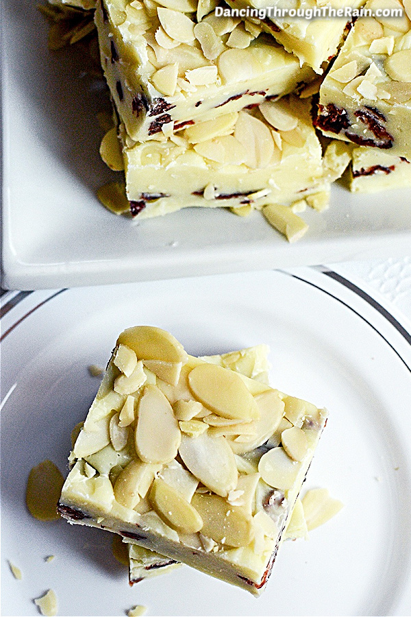 Two pieces of White Chocolate Cranberry Fudge with Almonds on a white plate next to another white plate of more