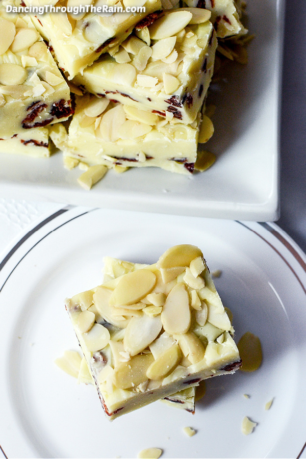 A piece of White Chocolate Cranberry Fudge with Almonds on a white plate next to a square white plate of more fudge