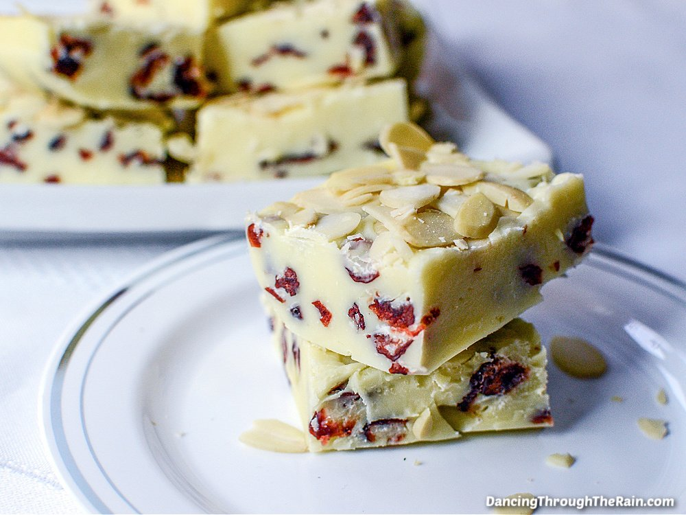 Two pieces of White Chocolate Cranberry Fudge on a white plate with another white plate with more pieces in the background