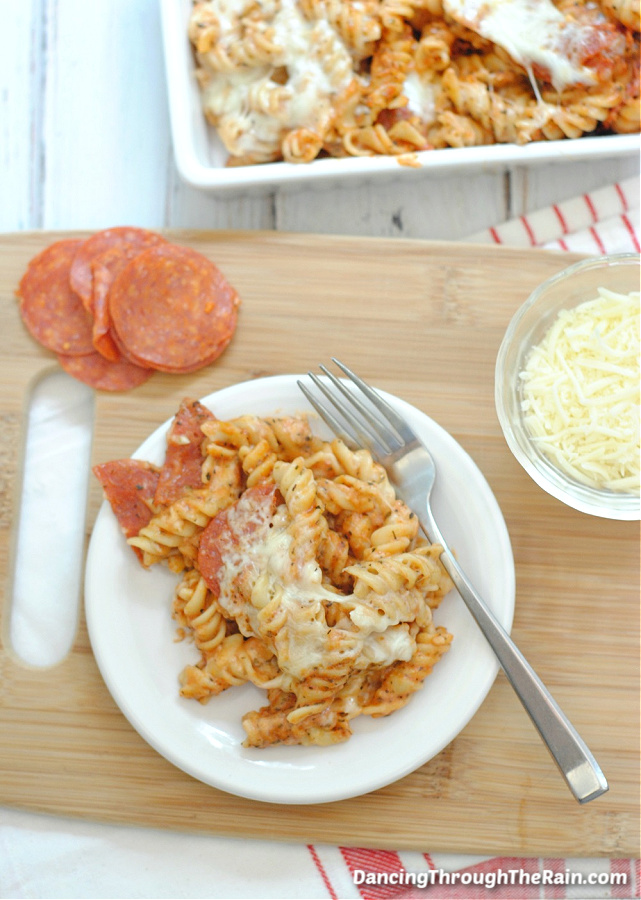 A white plate with a scoop of Easy Pepperoni Pasta Bake on a wooden cutting board next to pepperoni slices and a clear bowl of mozzarella cheese