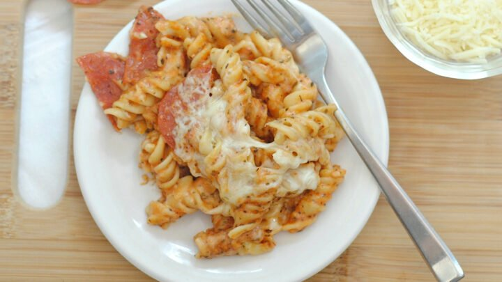 A plate of Pepperoni Pasta Bake on a wooden cutting board with a metal fork