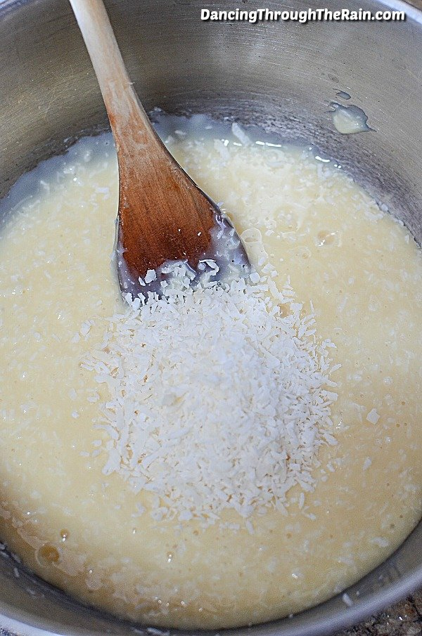 Sweetened condensed milk with coconut in a mixing bowl with spoon