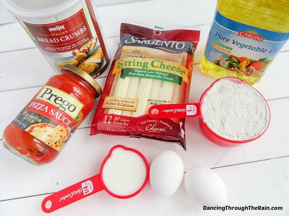 Sargento string cheese, bread crumbs, Prego pasta sauce, vegetable oil, two eggs, flour in a red measuring cup and milk in a red measuring cup on a white table