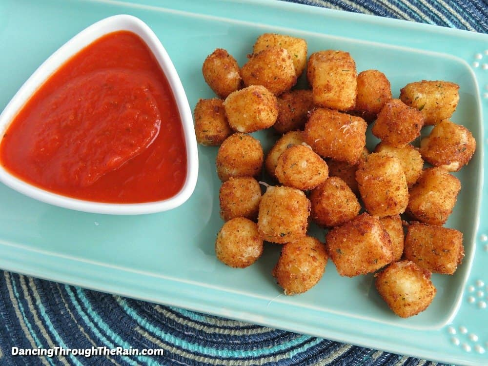Easy fried cheese bites on a light blue plate next to a white bowl of marinara