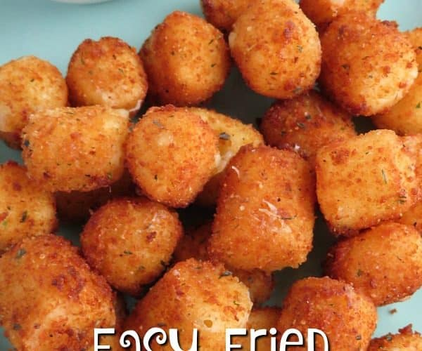 Easy fried cheese bites on a light blue plate next to a white dish with marinara sauce