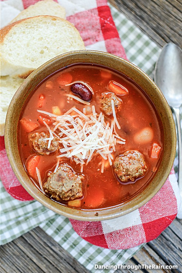 Easy Slow Cooker Meatball Soup in a brown bowl next to two slices of Italian bread on a table with a red and white hot mitt, and a green and white fabric napkin
