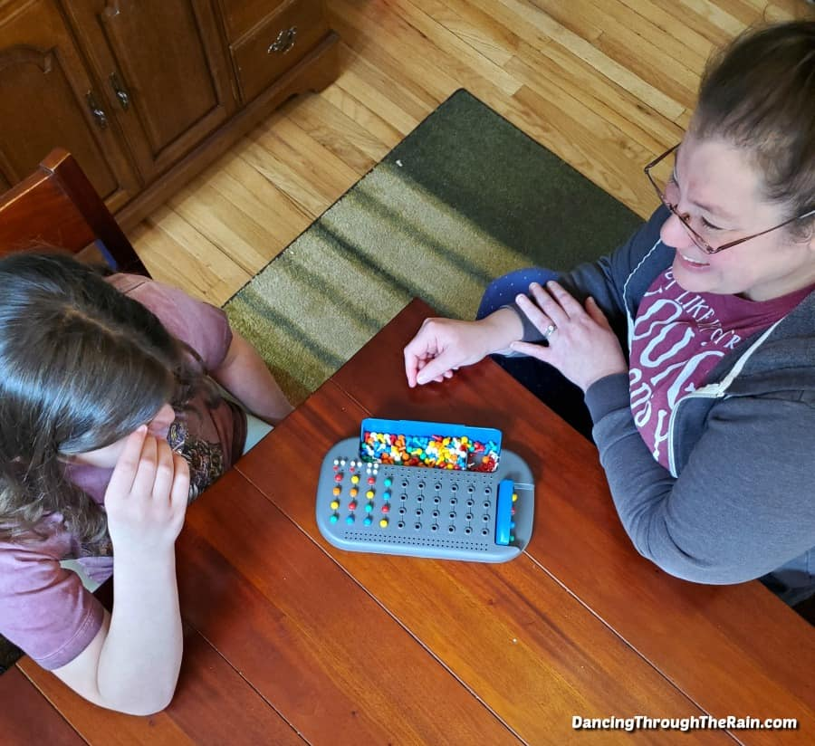 Alli and girl playing a game at a wooden table