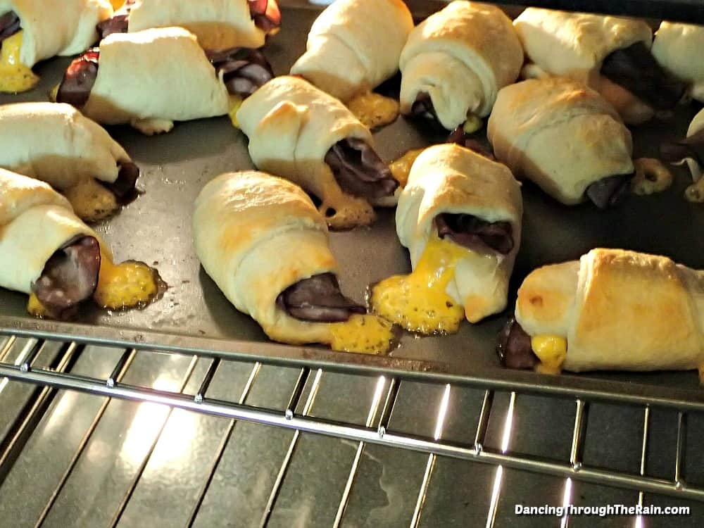 A bunch of roast beef and cheddar crescent rolls baked on a baking sheet in an oven