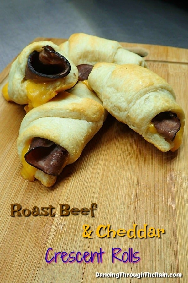 Three Roast Beef and Cheddar Crescent Rolls on a wooden cutting board