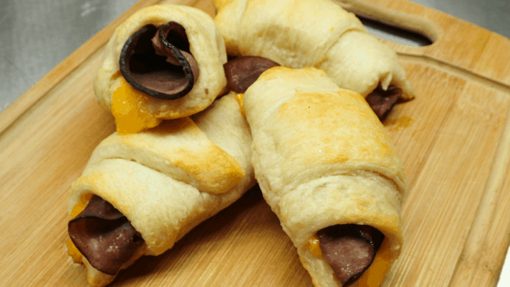 Four roast beef and cheddar crescent rolls stacked on a wooden cutting board