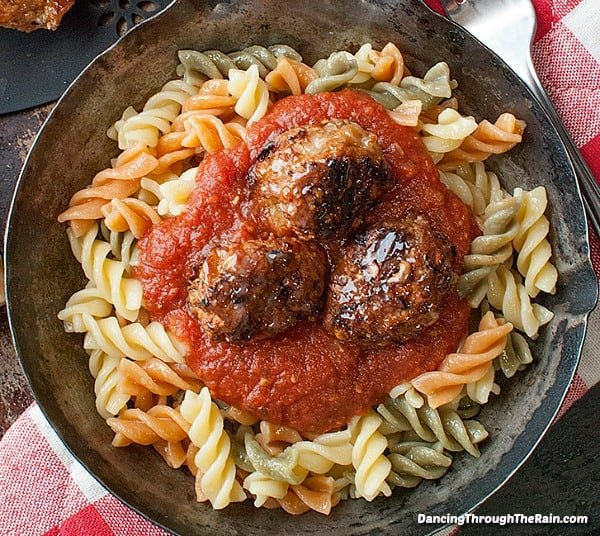 Three baked chicken meatballs on top of tri-colored pasta and pasta sauce in a cast iron pan