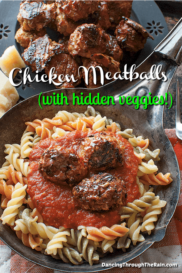 Baked chicken meatballs in a cast iron skillet on top of tri-colored pasta and pasta sauce, next to a plate with more chicken meatballs