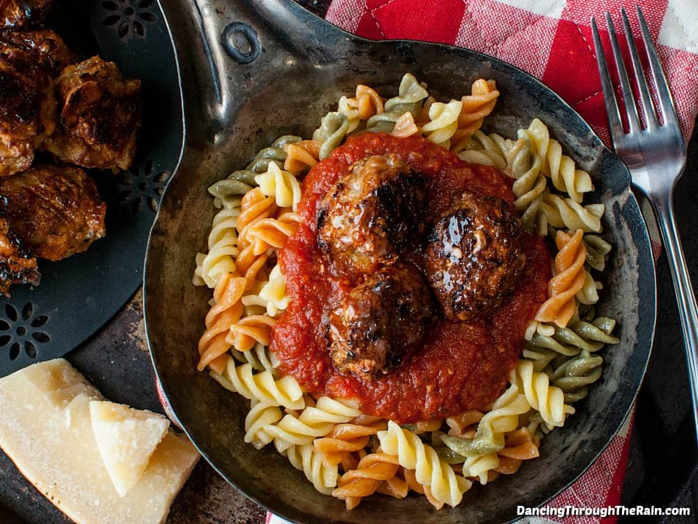 Three baked chicken meatballs on top of tri-colored pasta with pasta sauce in a cast iron pan next to a plate with more baked chicken meatballs