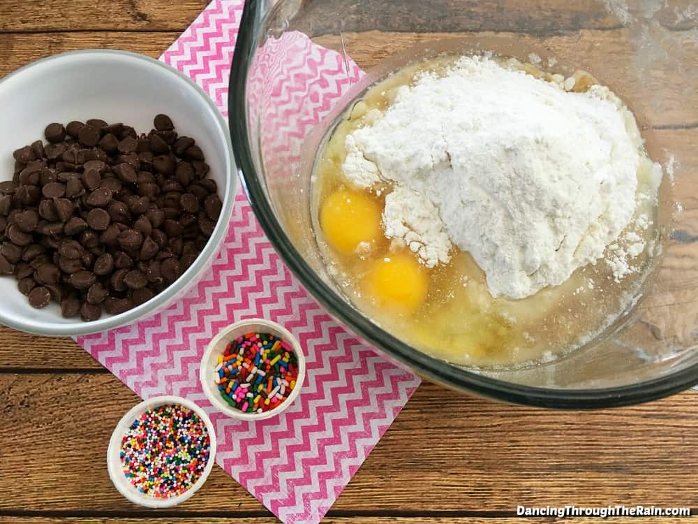 A clear bowl with cracked eggs, cake mix, and powder inside next to bowls of chocolate chips, straight sprinkles and ball sprinkles on a wooden table and a pink zig zag napkin