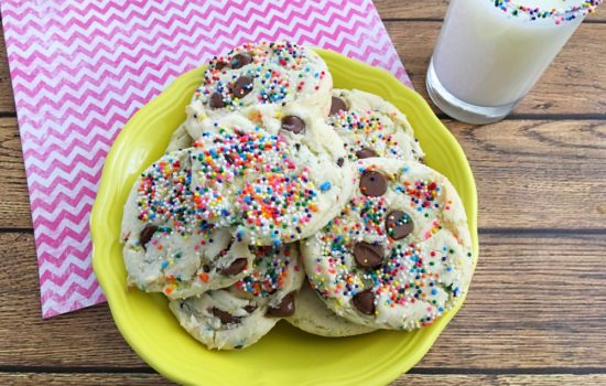 Funfetti Cake Mix Cookies on a yellow plate under a pink zig zag napkin on a wooden table