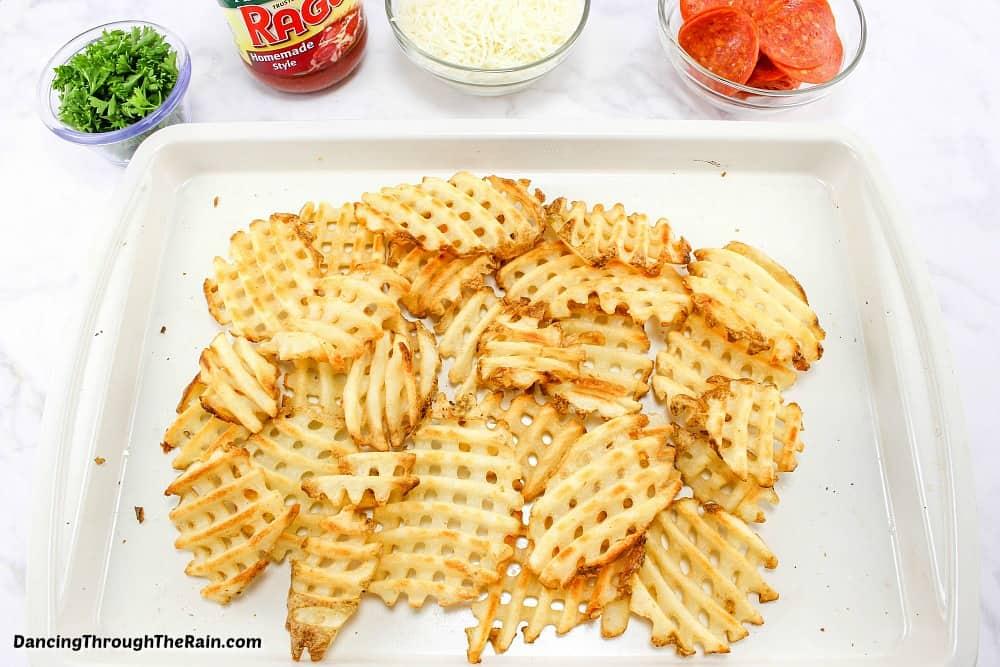 Baked waffle fries on a white baking sheet