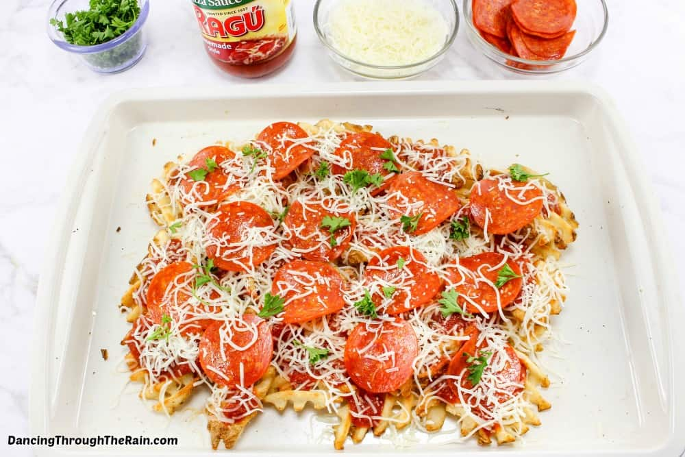 Pizza waffle fries assembled on a white baking sheet before going into the oven