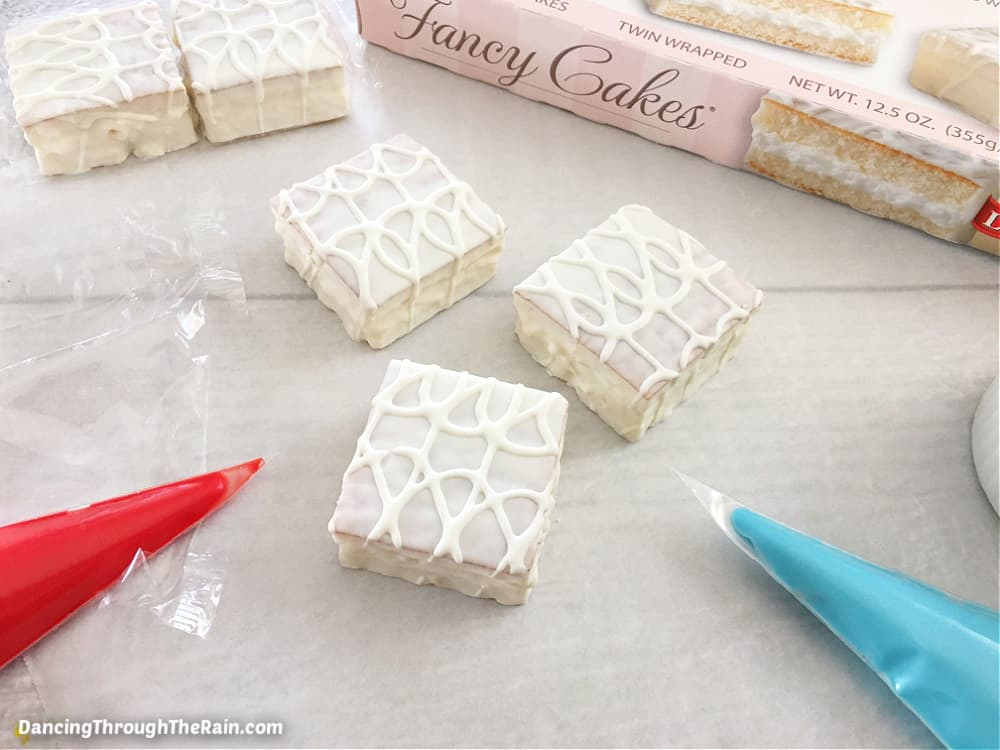 Five Little Debbie Fancy Cakes unwrapped on a white wooden table next to a red and a blue pastry bag