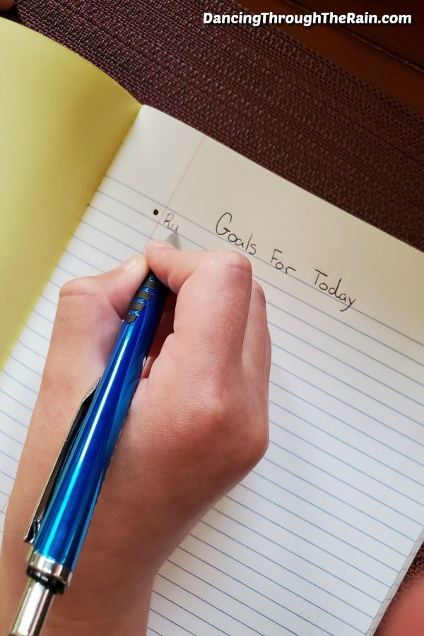 A hand holding a pen writing in a journal with lined paper about the goals for the day