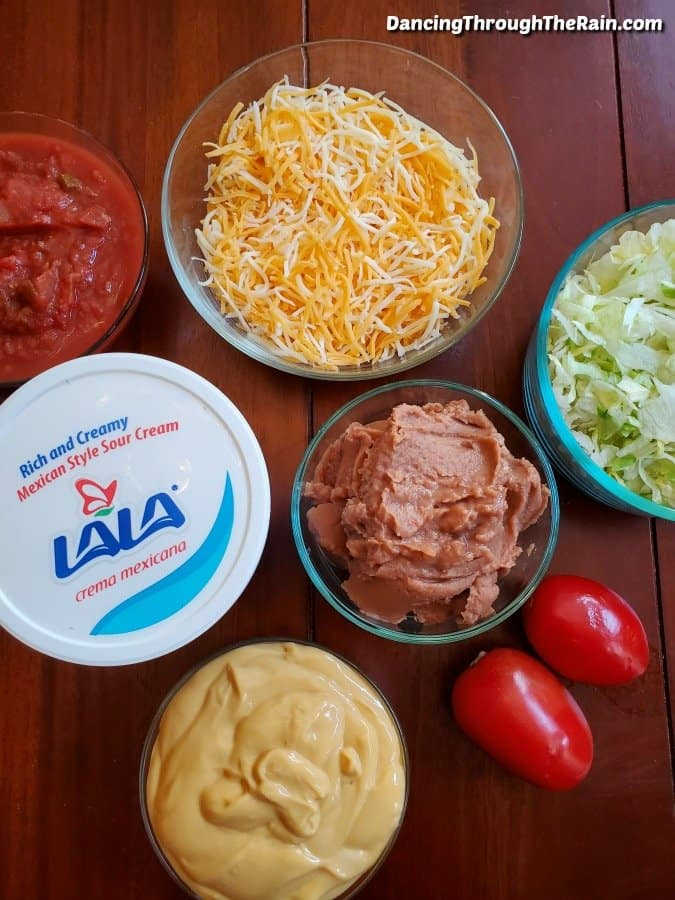 Salsa, shredded cheese, refried beans, shredded lettuce, cheese sauce in clear glass bowls, two Roma tomatoes and LALA Crema Mexicana on a wood table