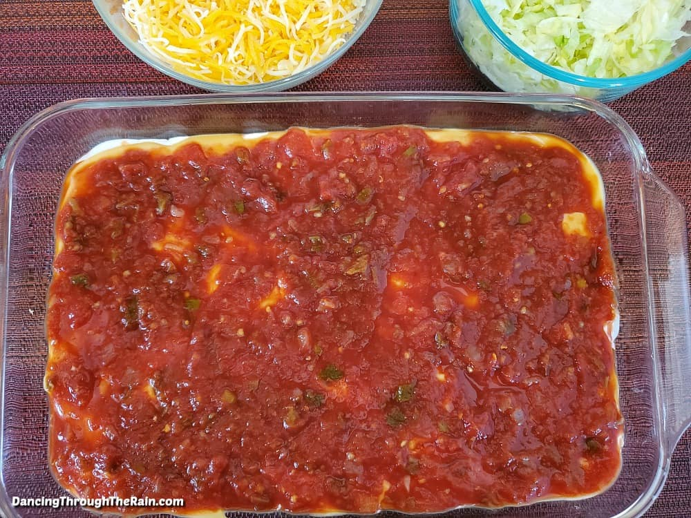 "A 9x13"" clear baking dish with salsa spread across cheese sauce and LALA Crema Mexicana, with glass bowls of shredded cheese and shredded lettuce above"