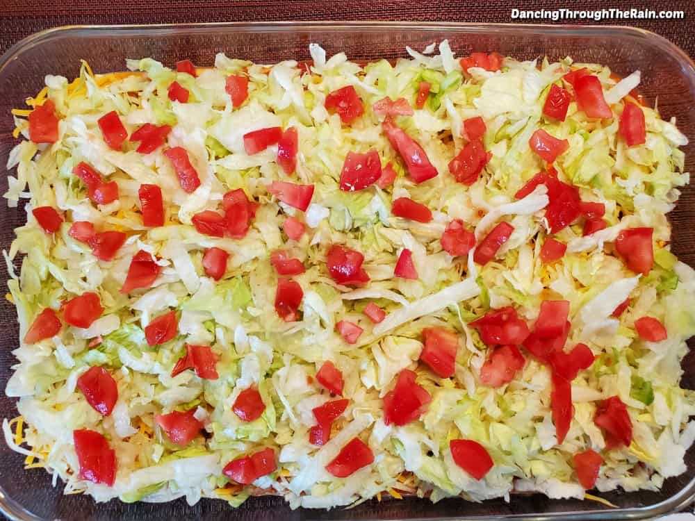 "A 9x13"" clear baking dish with shredded lettuce and diced tomatoes spread across the top"
