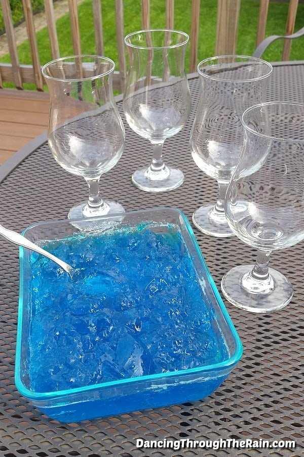 A clear square baking dish full of blue Jello with a metal spoon inside next to four parfait glasses on a metal table