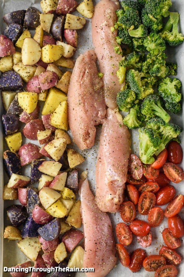 A sheet pan lined with parchment paper topped with cut fingerling potatoes on the left, four pieces of raw chicken in the middle and raw broccoli and tomatoes on the right