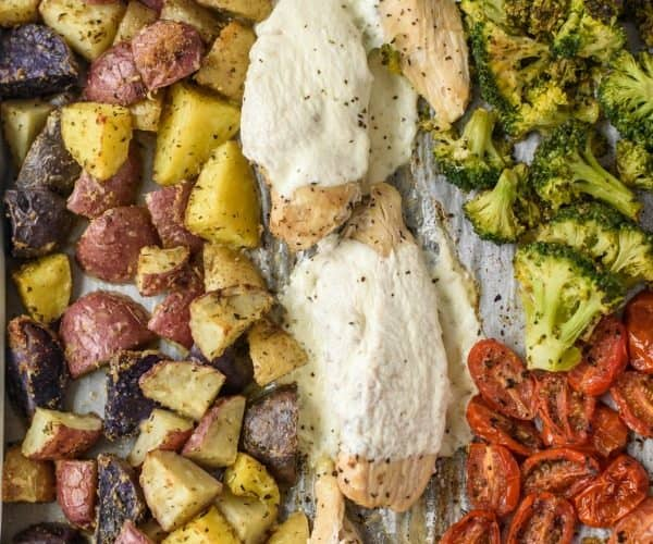 A sheet pan lined with parchment paper with cooked fingerling potatoes on the left, cooked mozzarella chicken down the middle and cooked broccoli and tomatoes on the right