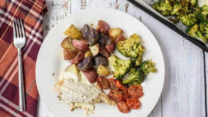 A white plate on a wooden table with mozzarella chicken, potatoes, tomatoes and broccoli next to a sheet pan and a red checked napkin with a fork on top