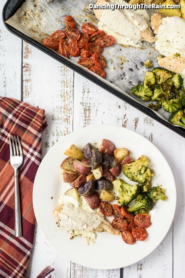 A red checkered napkin with a fork on top, next to a white plate with mozzarella chicken, cooked potatoes, broccoli and tomatoes on a wooden table next to a sheet pan with the rest of the cooked ingredients
