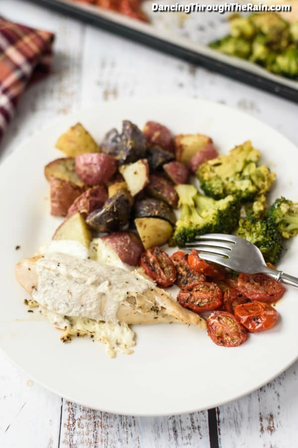 A white plate with Mozzarella Chicken, potatoes, broccoli, tomatoes and a fork on top of a wood table next to the sheet pan