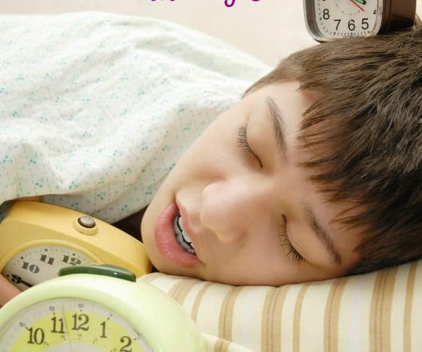 A child sleeping in bed with three alarm clocks