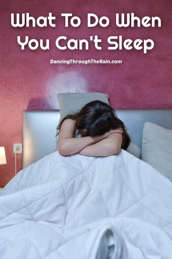 A woman with her head in her arms while sitting on a bed with white covers and the words What To Do When You Can't Sleep