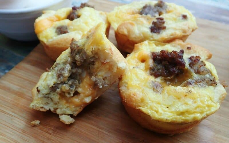 Four Easy Muffin Tin Sausage Quiche Cups on a wooden cutting board with one cut in half