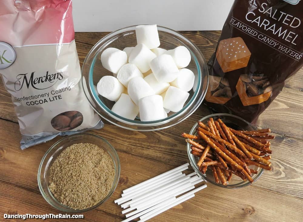 Bowls full of marshmallows, pretzel sticks, brown sugar and bags of chocolate melts and salted caramel melts on a wooden table