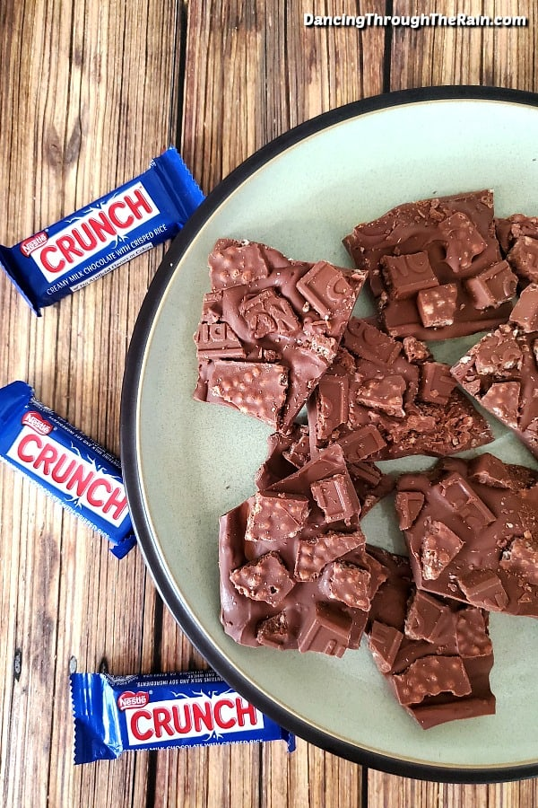 Many pieces of Crunch Bar Candy Bark on a mint green plate on a wooden table next to three wrapped fun size Nestle Crunch Bars