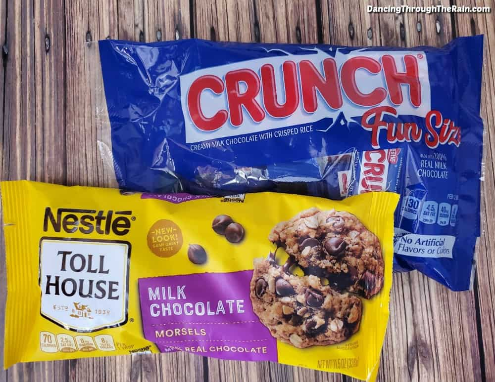 A bag of fun size Nestle Crunch Candy and a bag of Nestle Toll House milk chocolate chips on a wooden table