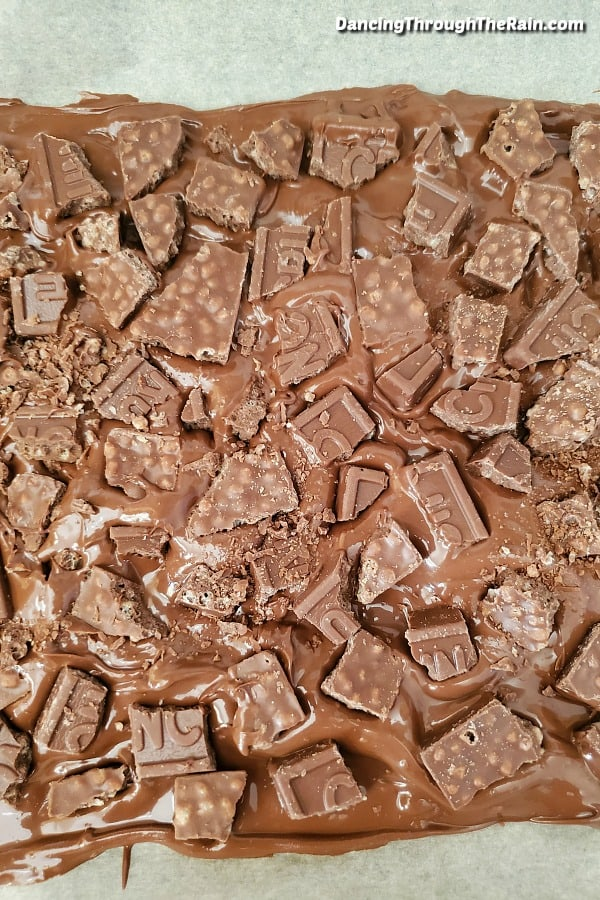 Melted milk chocolate with broken pieces of Nestle Crunch Bars pushed in on a baking sheet