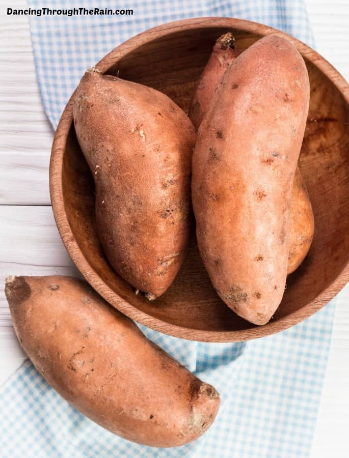 A wooden bowl full of three sweet potatoes on a wooden table next to another sweet potato