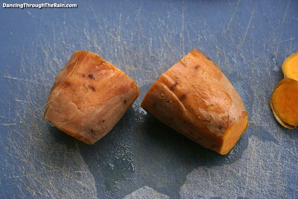 A sweet potato cut in half with the ends cut off on a blue cutting board