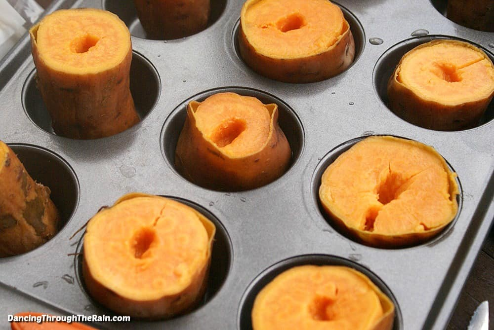 A muffin tin with nine visible sweet potato halves with holes poked in the middle of each