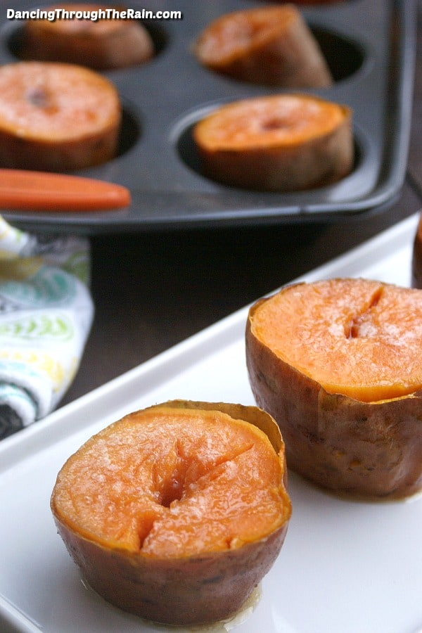Two easy muffin tin sweet potatoes on a rectangular white plate in front of a muffin tin with other sweet potato halves in it