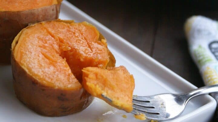 A white rectangular plate with two easy muffin tin sweet potatoes, one of which is being cut with a fork