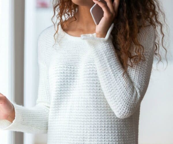 An African American woman wearing a white sweater and listening to a cell phone