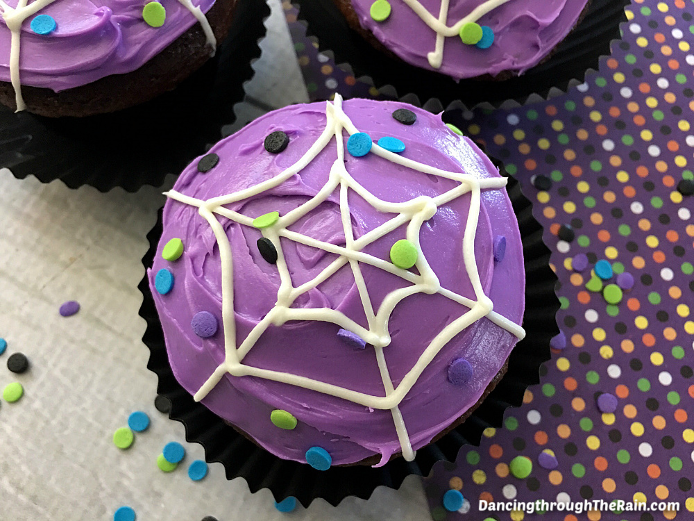 Three Spiderweb Cupcakes on a table with a purple polka dot placemat